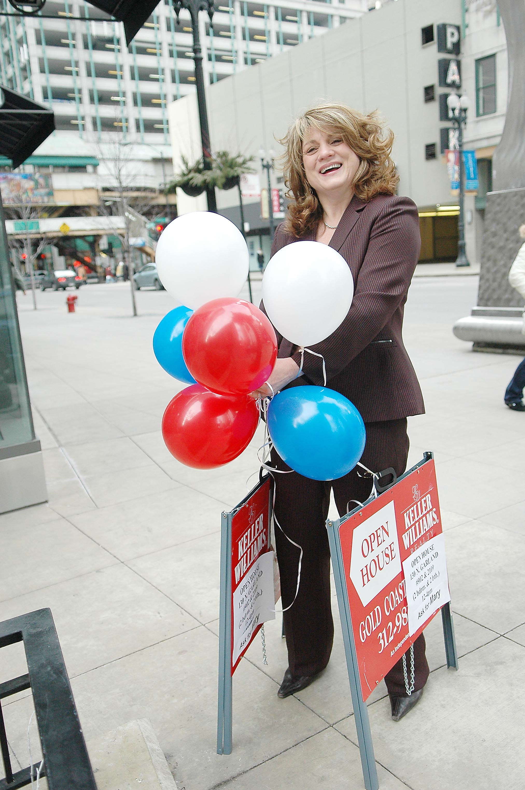On Washington Street, Keller Williams agent Mary Vallender struggles with balloons advertising an open house at The Heritage at Millennium Park, 130 N Garland Ct.