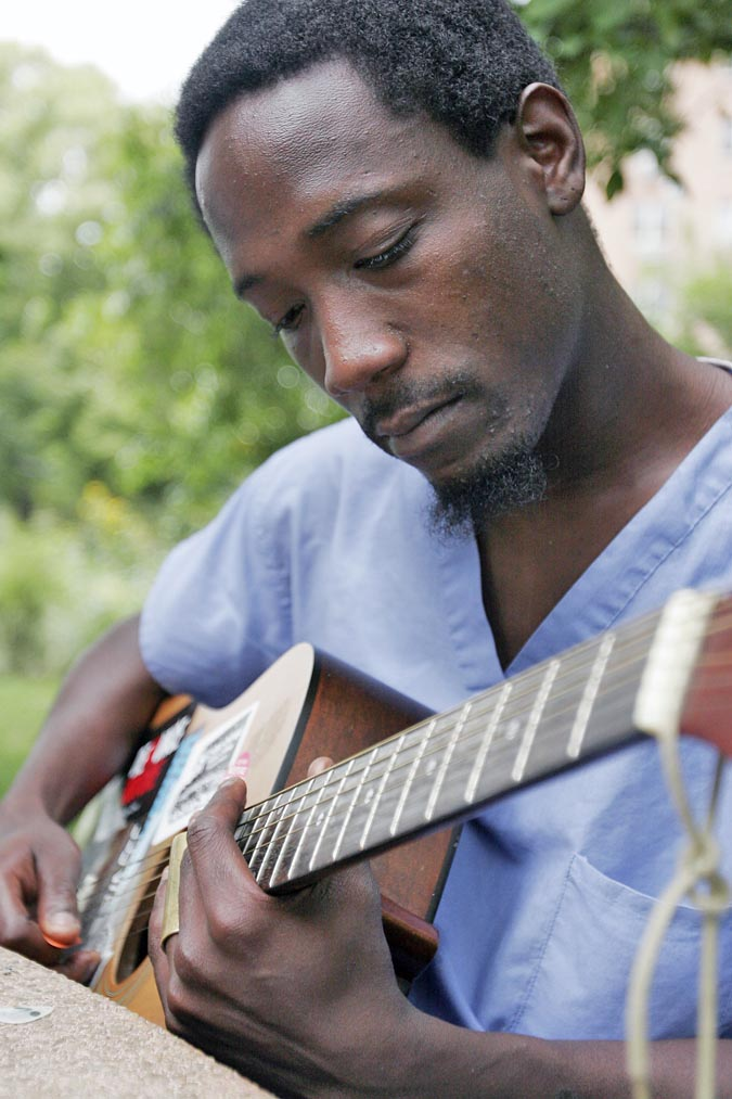 Shannon Fortune strums his guitar in Wicker Park.